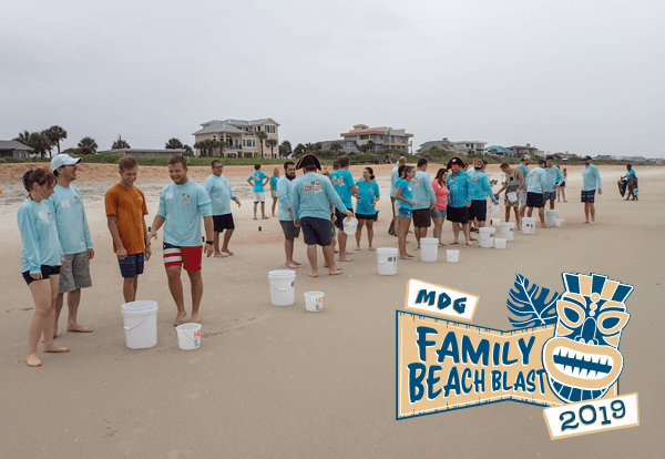 MDG staff and family gathered in groups on the beach with white buckets and the Family Beach Blast logo overlayed