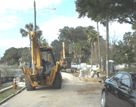 Excavator parked on the site of the road in front of a construction zone in downtown St. Augustine