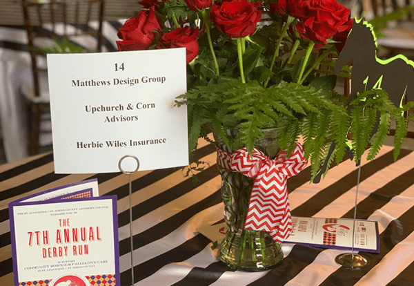 MDG table marker on a striped table next to a bouquet of red roses