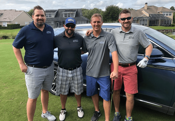 Four MDG men standing on a golf course in front of a car dressed in gold shorts and polos