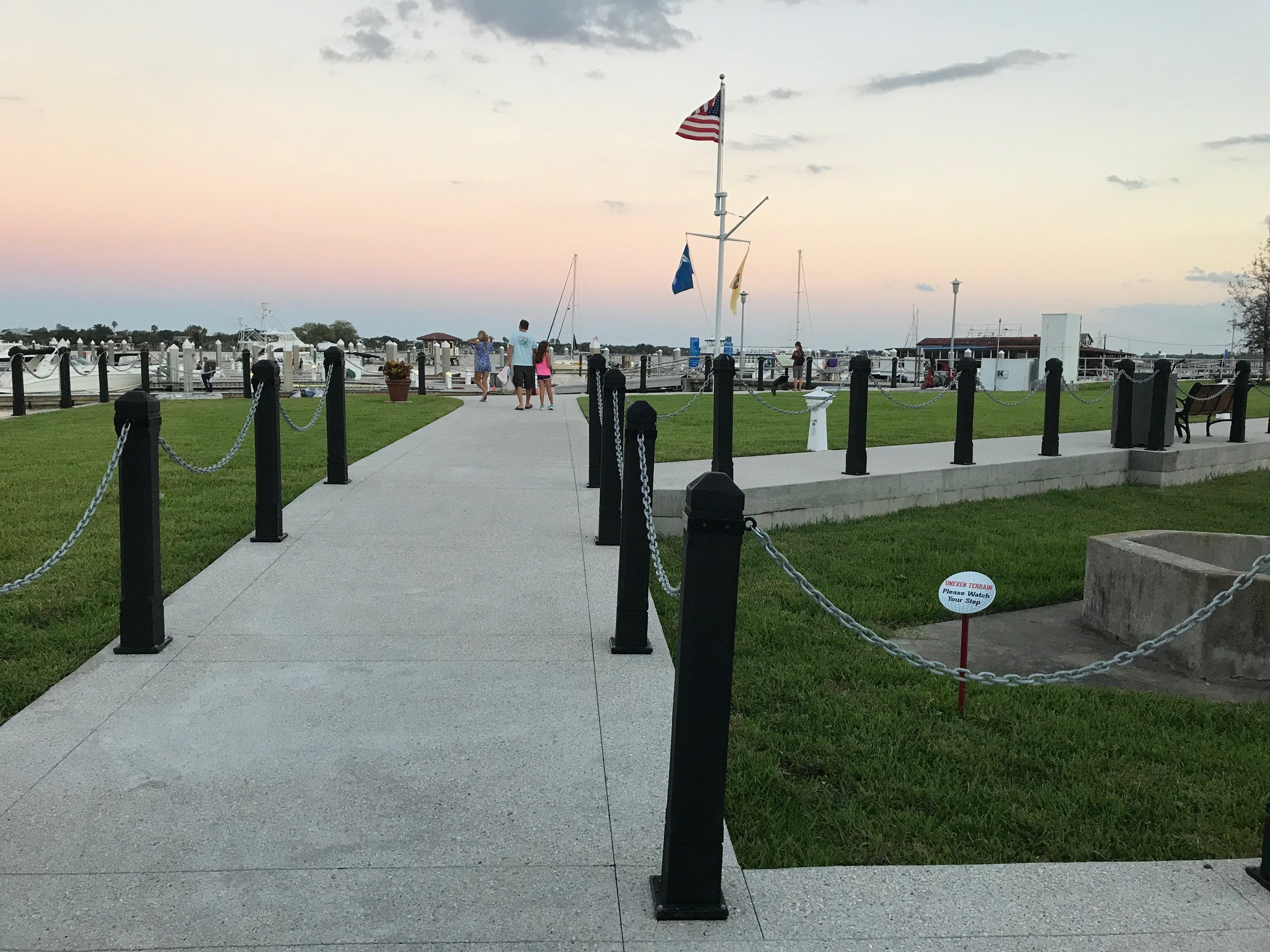 The bayfront park in downtown City of St. Augustine showing the sidewalks lined with poles and chains and a family in the background next to the American flag