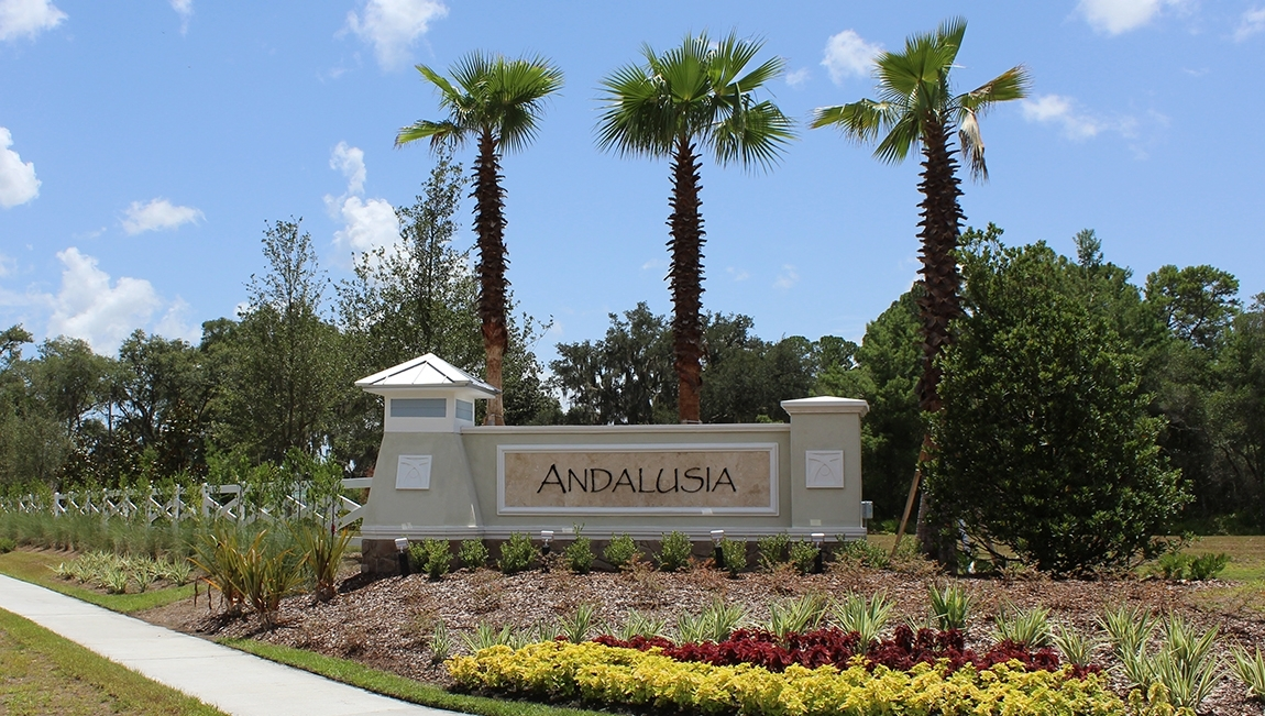 Andalusia Subdivision monument with the landscape design consisting of red and yellow flowers, green shrubbery, and palm trees