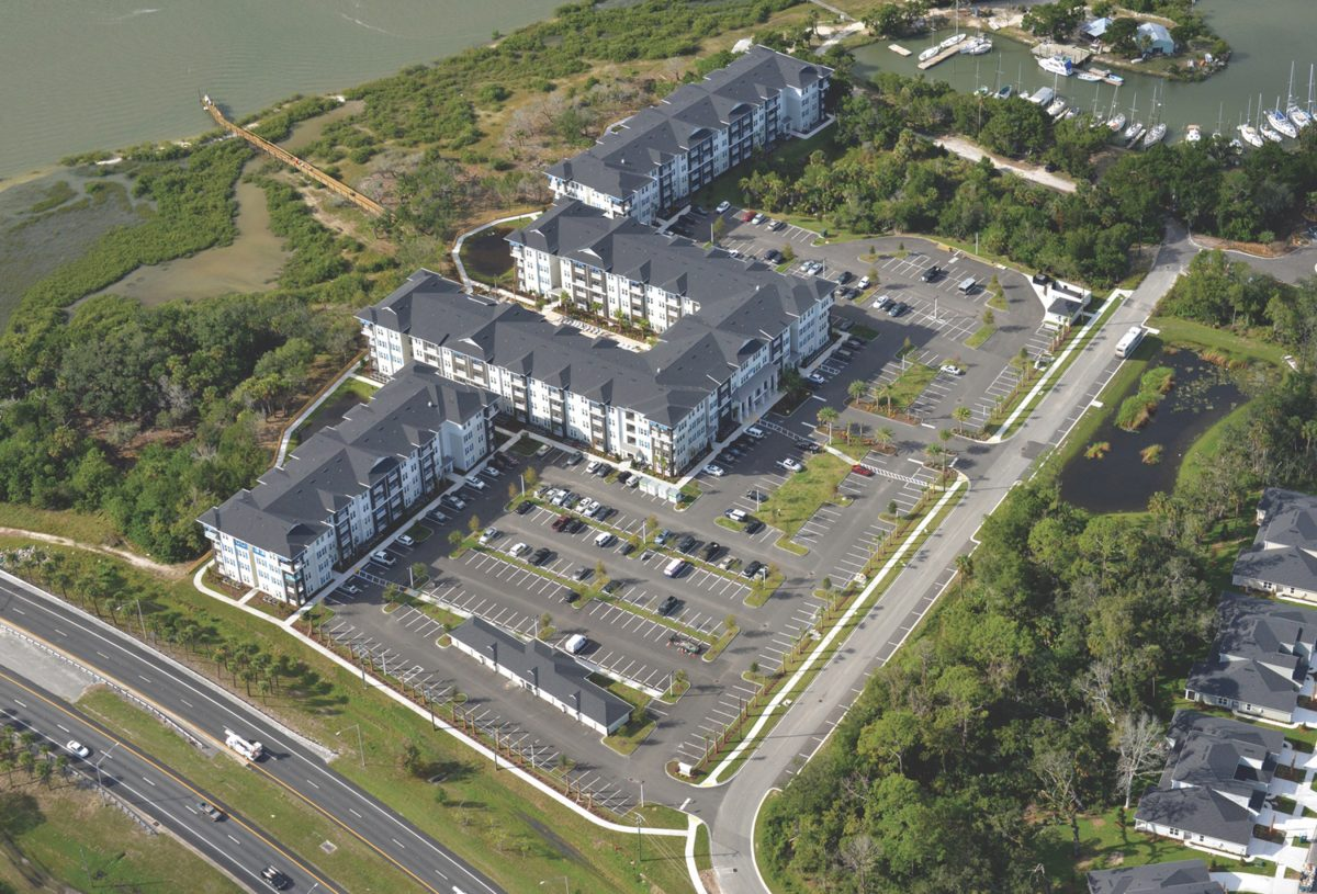 Aerial photo of the Antigua Apartments. Showing the parking and large apartments and the water front in the background
