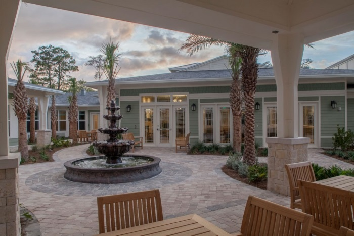 Patio of Arbor Terrace with laid stone flooring, patio tables and chairs, and palm trees.