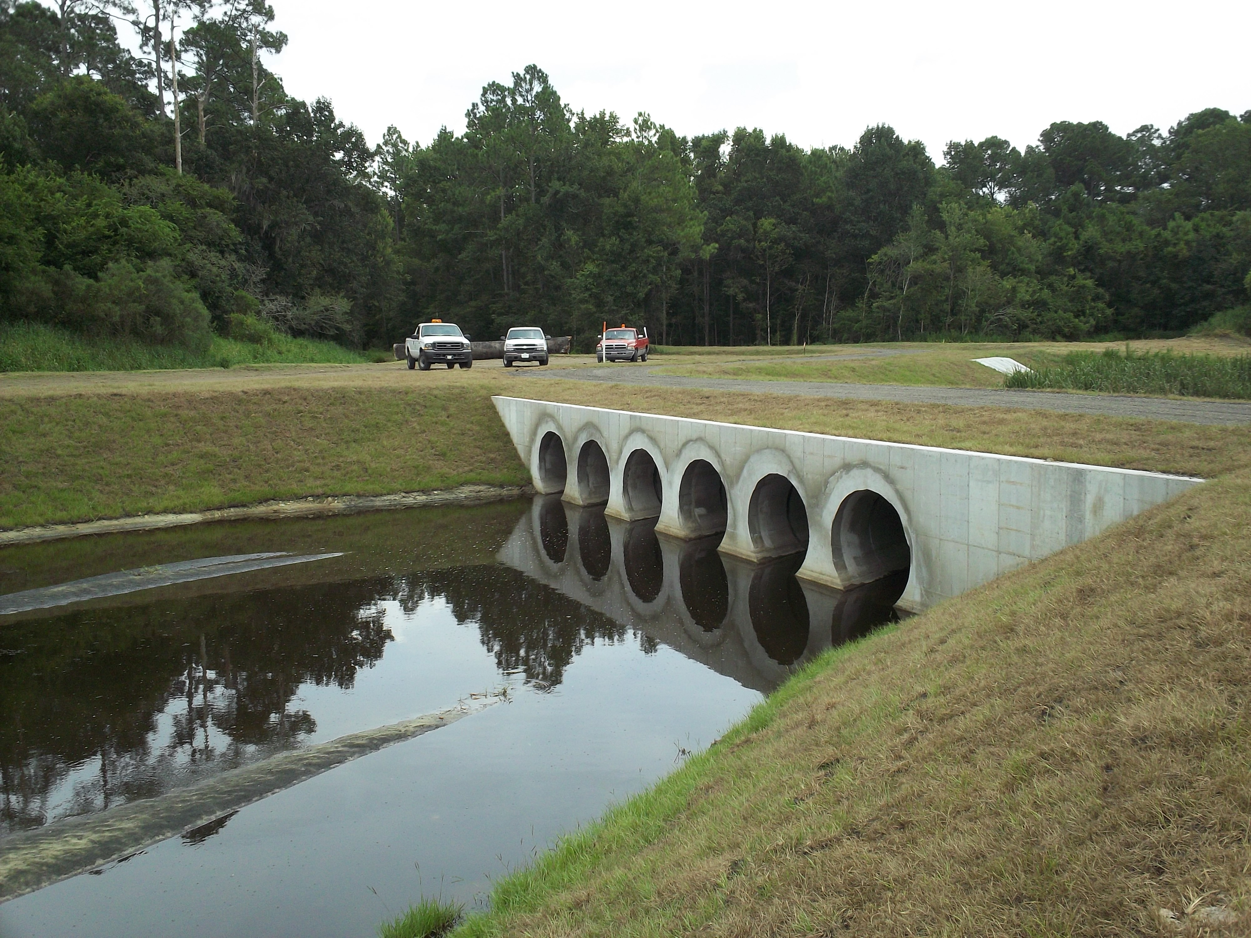 The completed culvert of the Ashley Outfall with water flowing underneath and three trucks in the background
