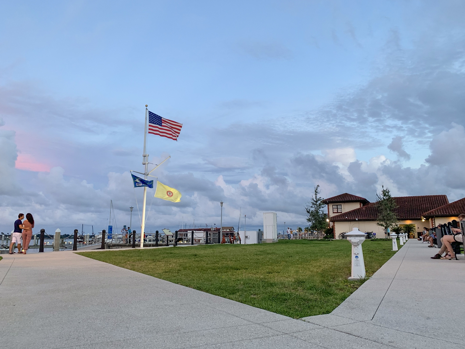 The bay front of St. Augustine showing people sitting at benches and over looking the water. A stormy evening sky falls behind the american flag and the marina structure