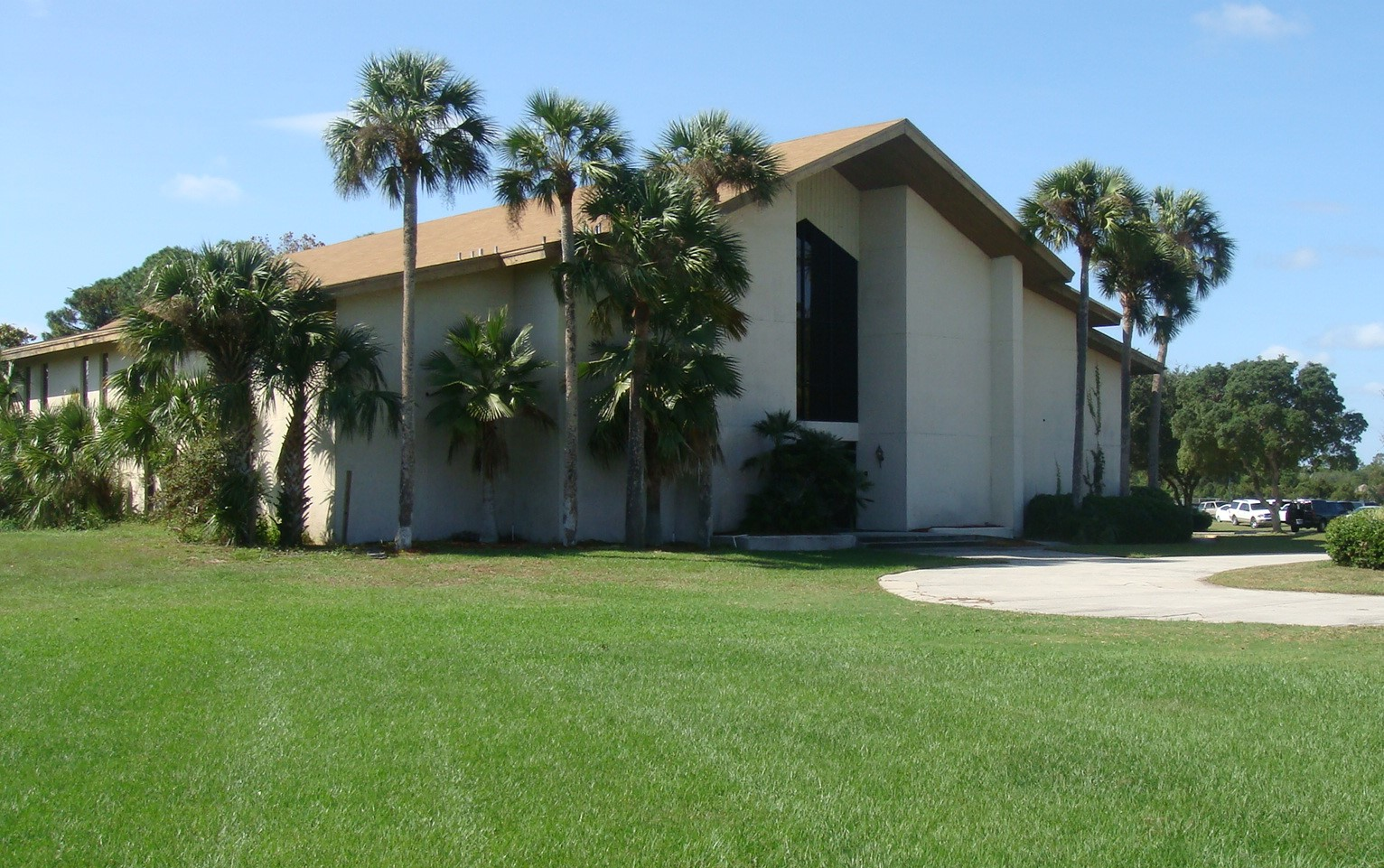 Photo of Cornerstone Community Center from an angle, showing its entrance surrounded by green grass and palm trees