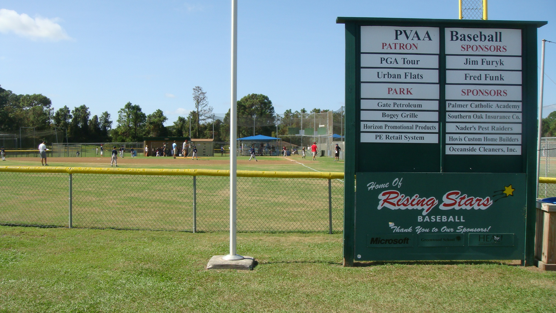 Photo of Cornerstone Park showing the baseball field with people playing ball and signage showing the park sponsors