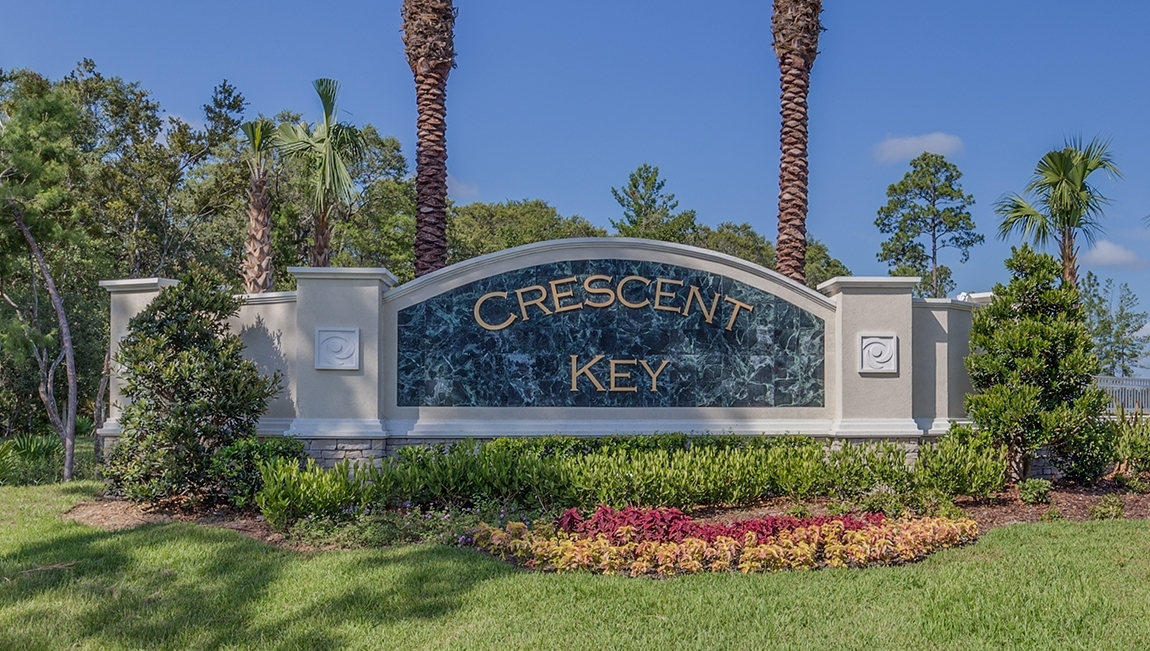 Crescent Key monument with the landscape design consisting of red and yellow flowers, green shrubbery, and palm trees