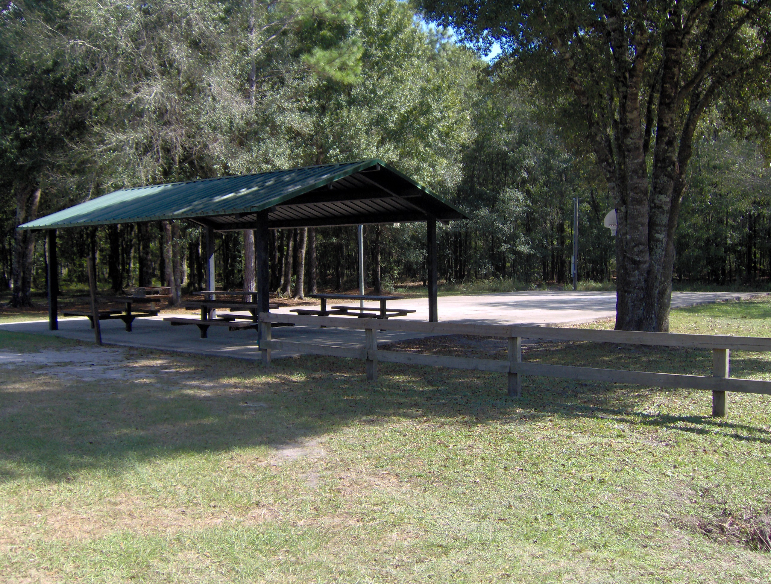 A green awning over some picnic benches by a basketball court surrounded by trees