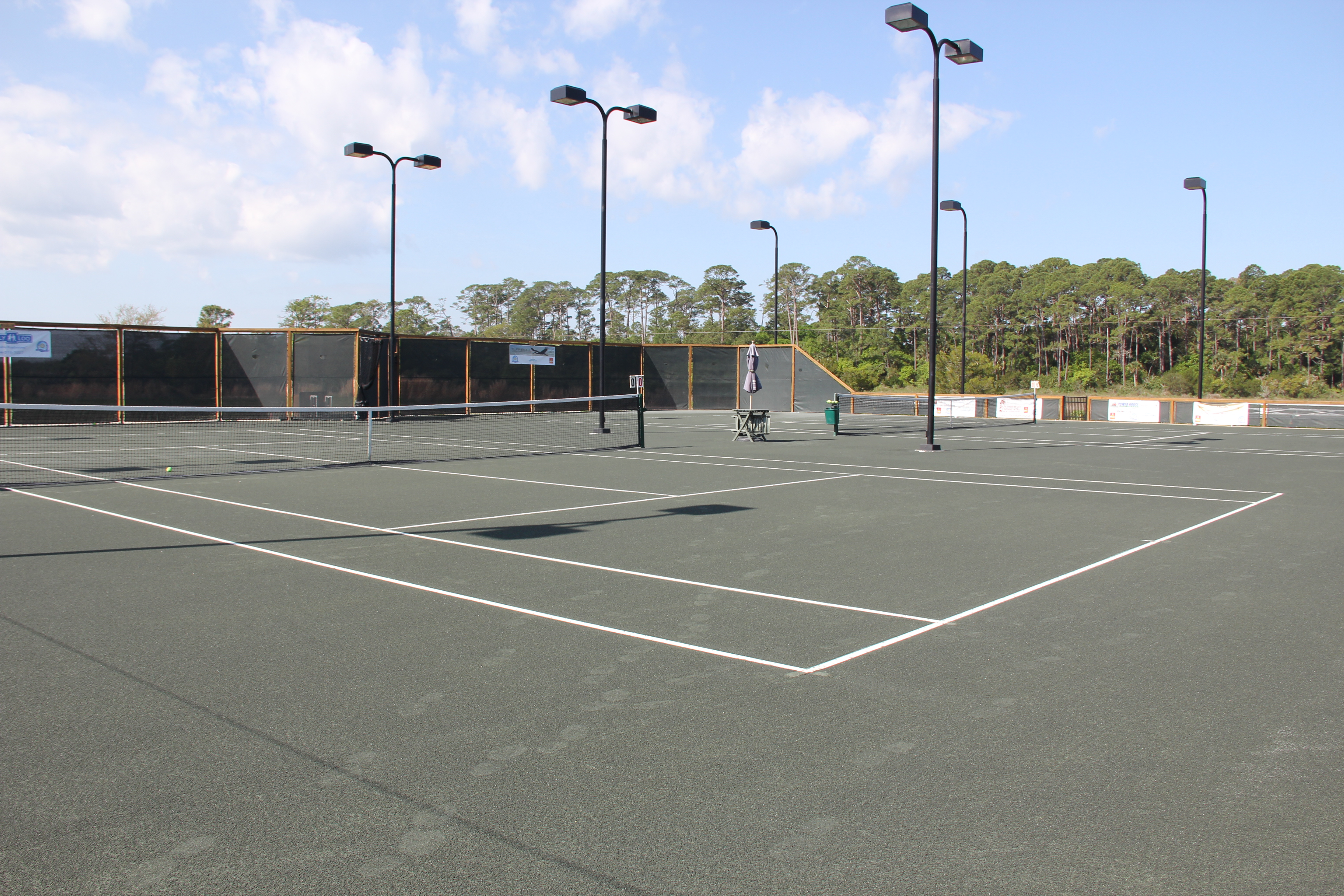 Photo of the new Harbour Island Tennis Court, showing the nets, lights, and fencing enclosure in the background with trees behind it.