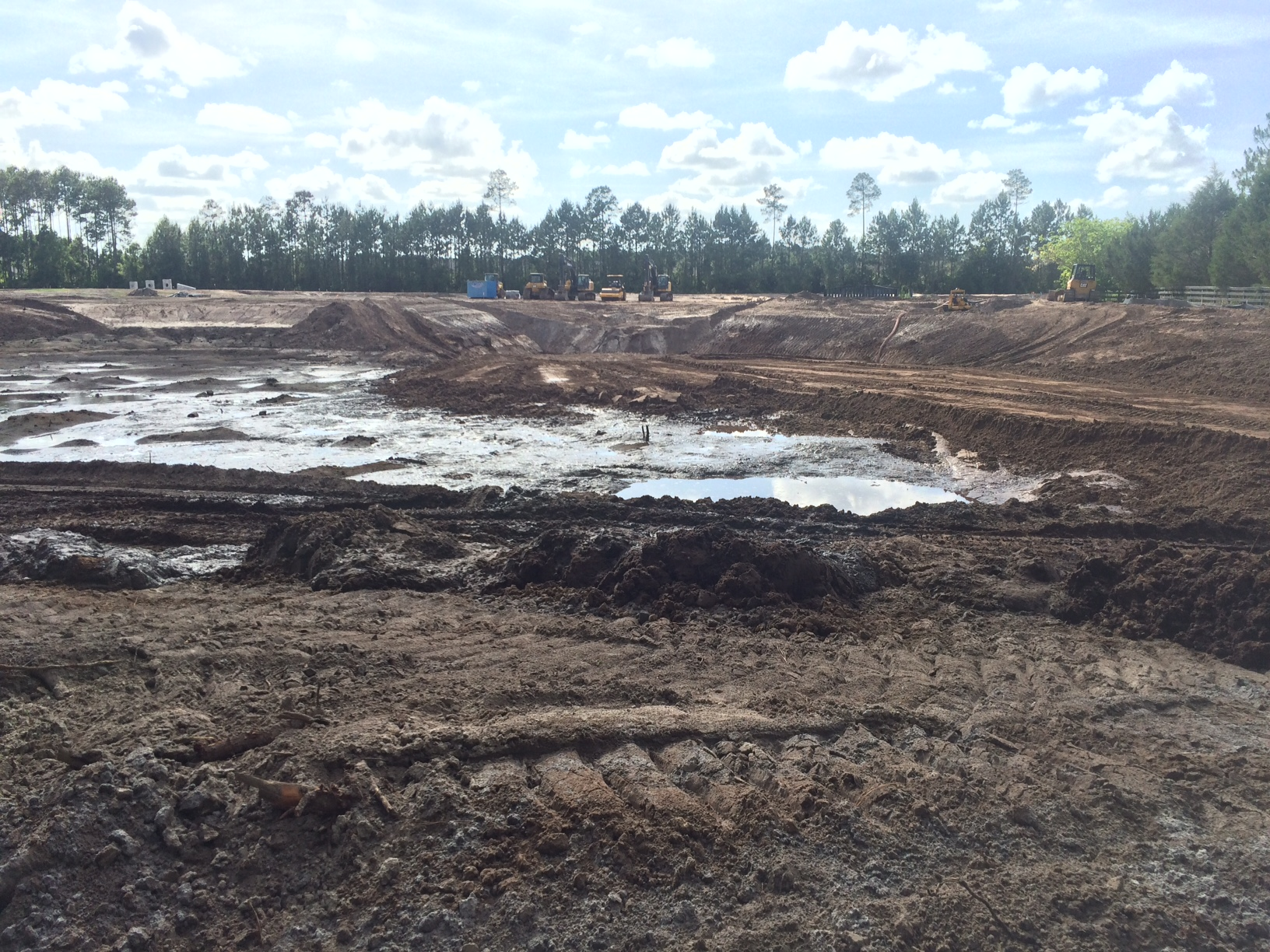 Photo of a borrow pit with a pool of mud at the center and tractors shown in the background