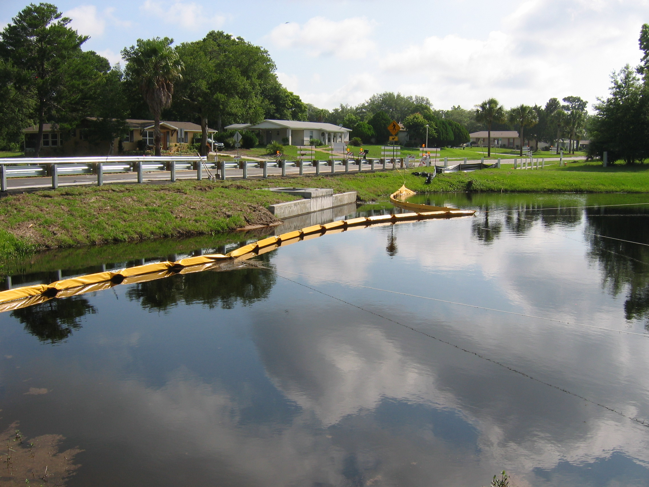 Photo of a turbidity barrier in a retention pond along the the roadway of a subdivision