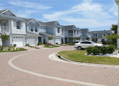 A brick road curving around a subdivision lined by large teal houses