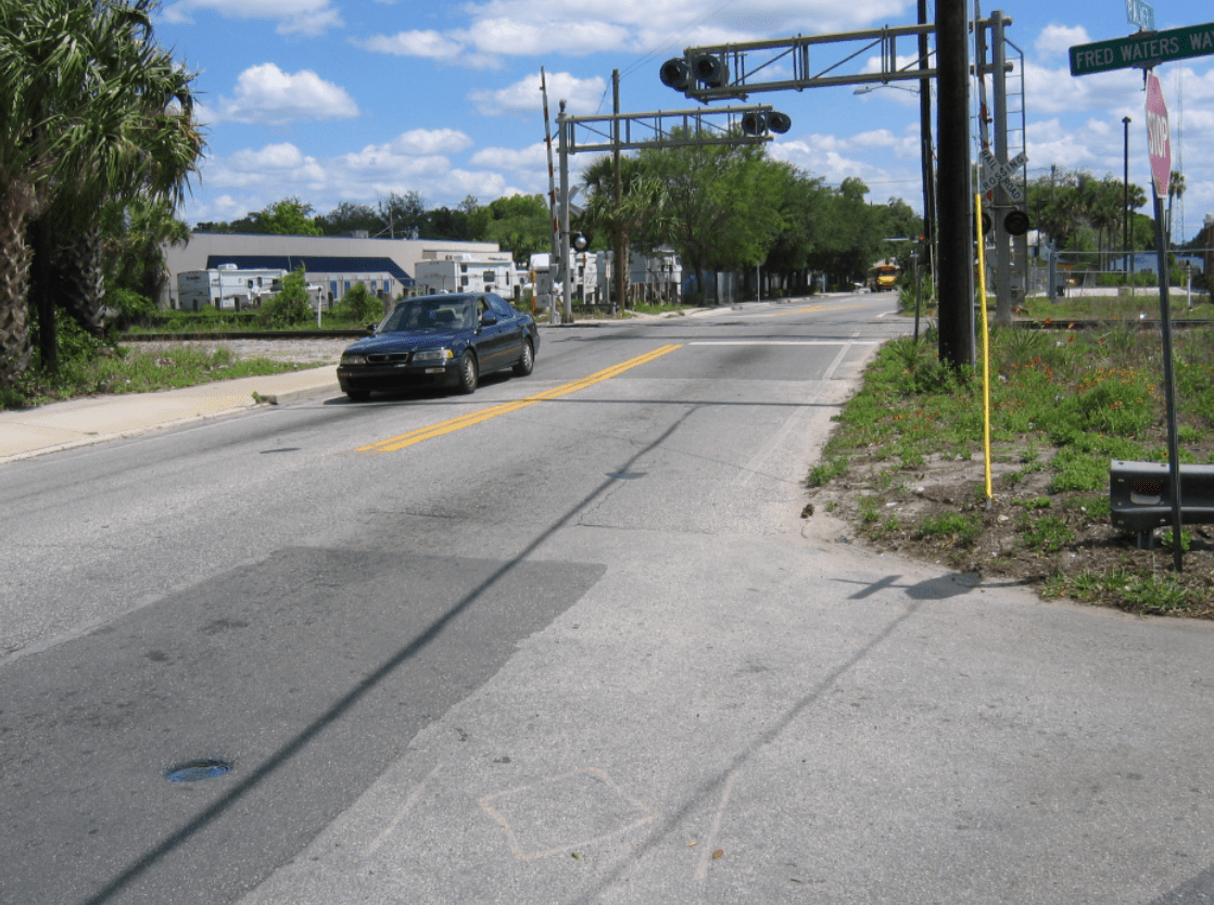 A photo of Palmer Street showing a black car driving over railroad tracks and a school bus off in the distance