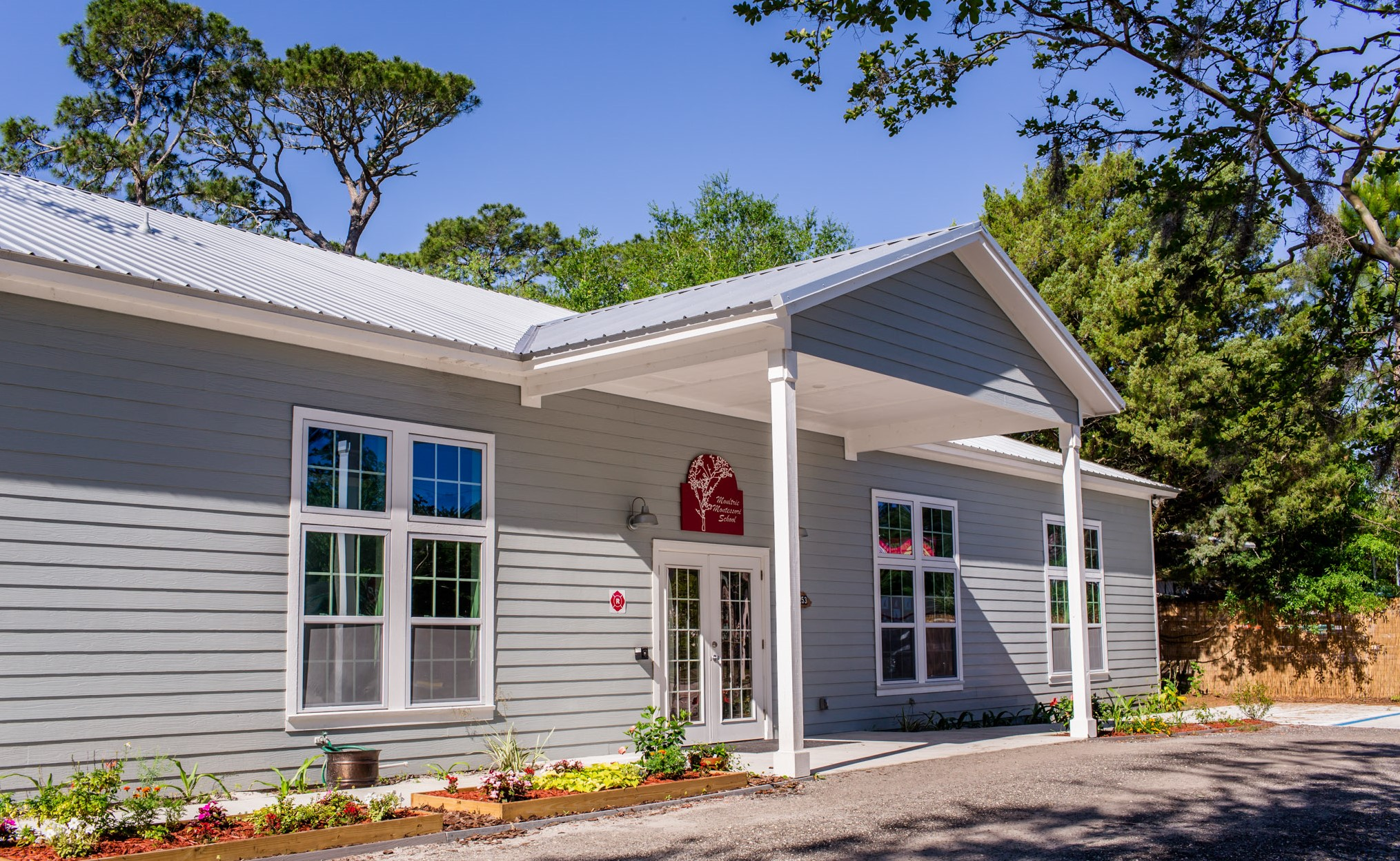 Entrance of the Moultrie Montessori school, the structure is in grey paneling with an awning with white pillars and the landscape out front with flowers and shrubs
