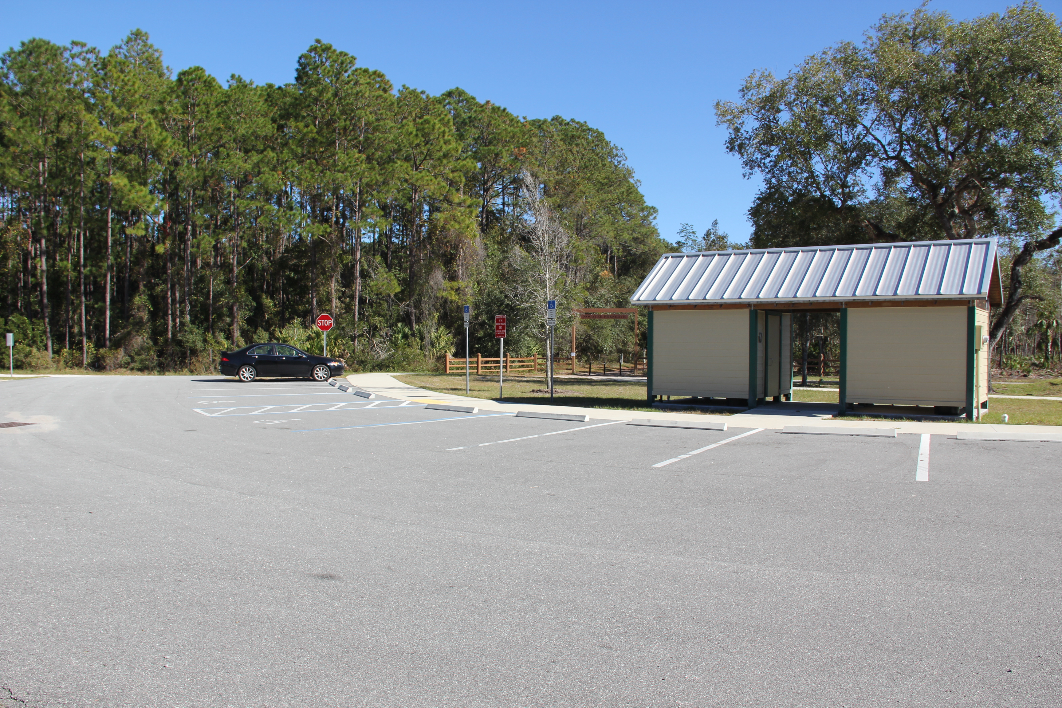 Photo of the parking lot for the Nocatee Trail Head Park. It shows the restrooms with tin roofing and a car parked in front of the trail entrance