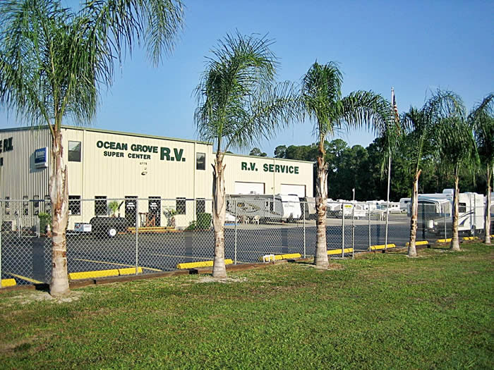 Photo of the Ocean Grove RV center showing the palm trees along the fenced in parking lot and the RV center in the background