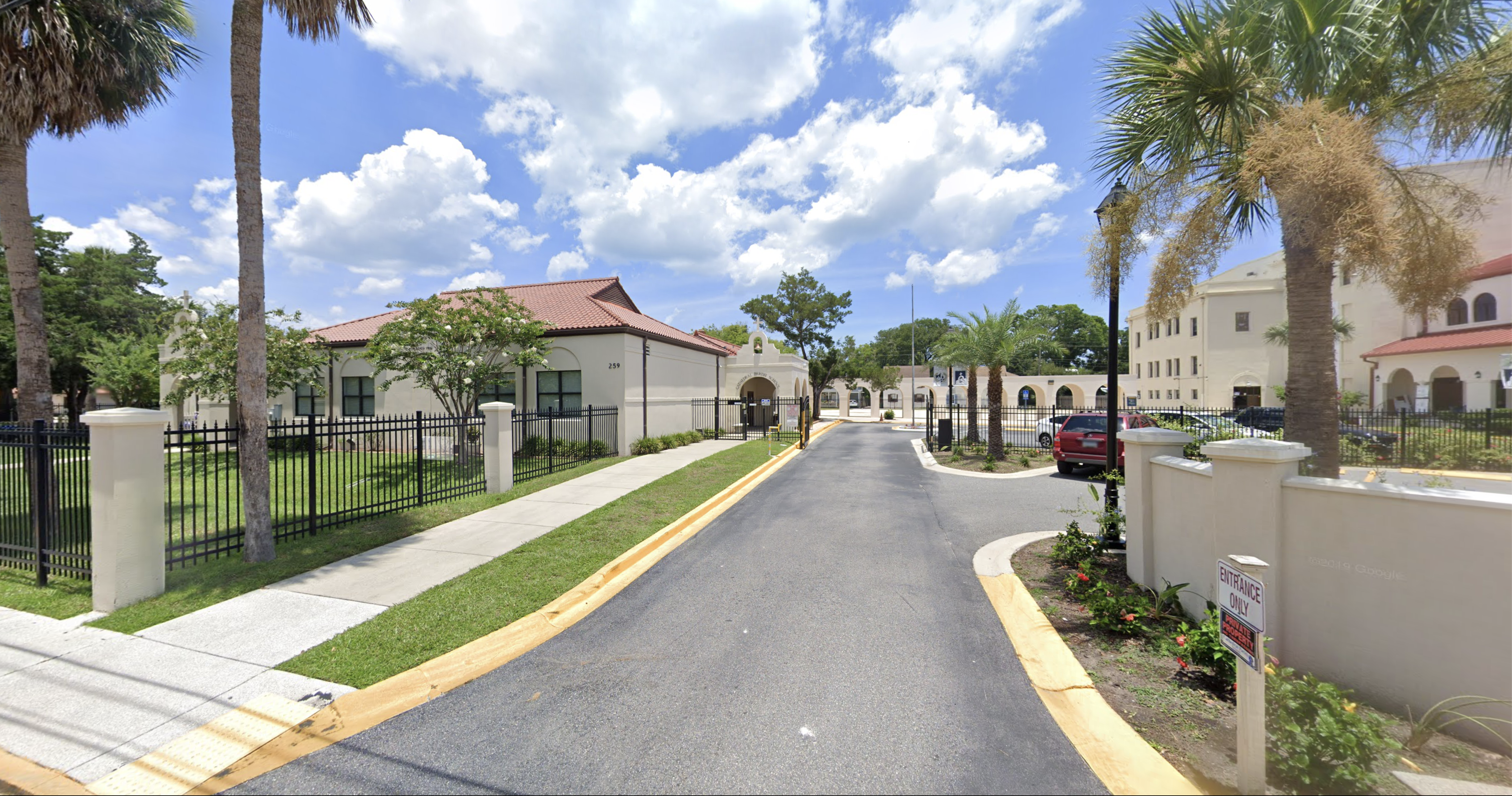 Driveway into the entrance of the Cathedral Parish School on a sunny day with palm trees and a tan, red roofed structures in the background