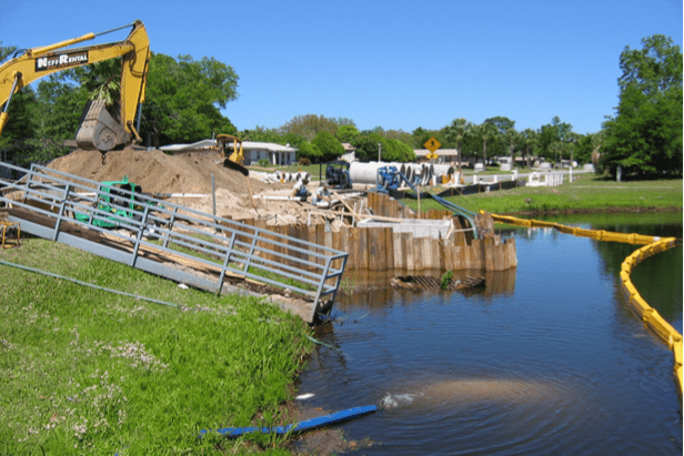 Construction work being performed for the Shores Boulevard Culvert Design. The photo shows tractors and cement piping along a body of water