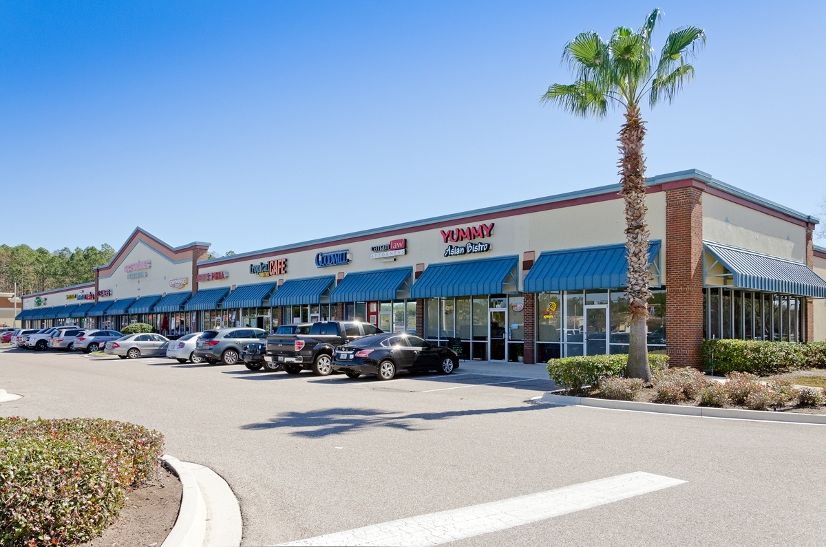 Photo of the Southlake plaza Shopping Center with cars parked in front by a palm tree