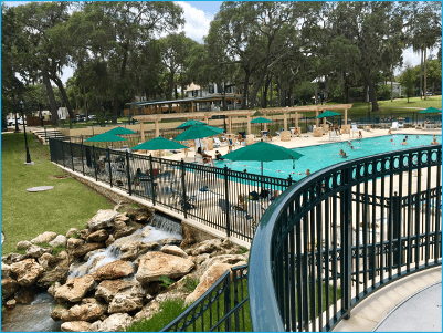 A photo of the Spring Park pool showing people swimming and lounging under green umbrellas. The pool has a waterfall with rocks on the side