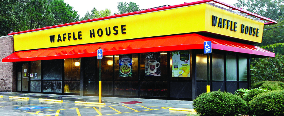 Photo of a brand new Waffle House storefront with its vibrant yellow and red branding along the top of the building