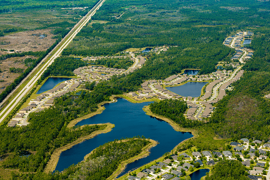 Aerial view of Las Calinas, a subdivision with lakes and a road.
