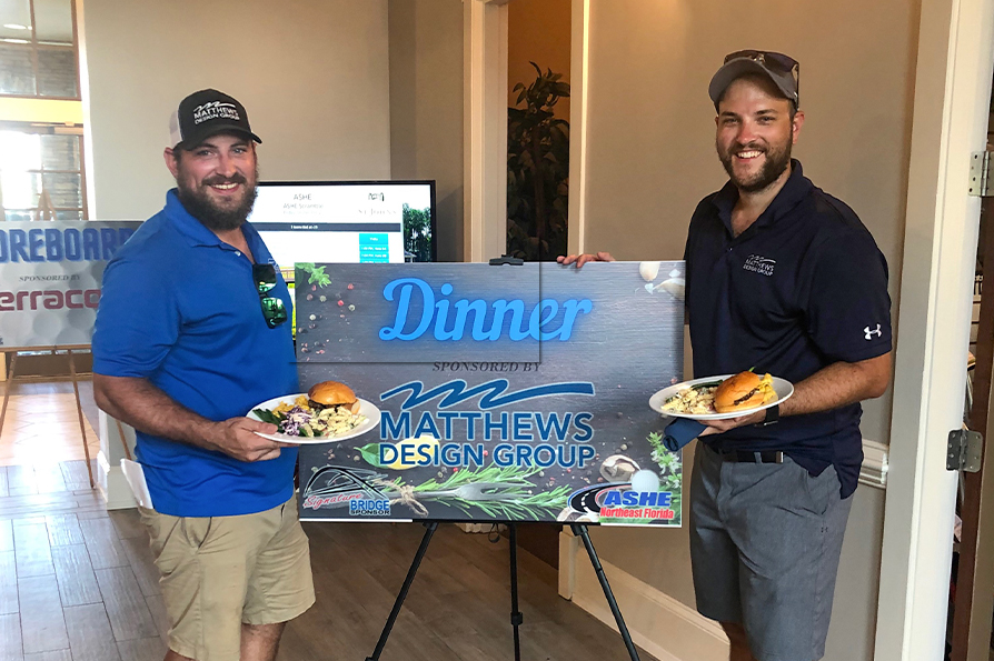 Team members in front of a dinner by Matthews Design Group Sign