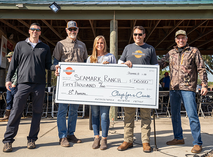 5 people smiling and holding a Clays for a cause check for $50,000.