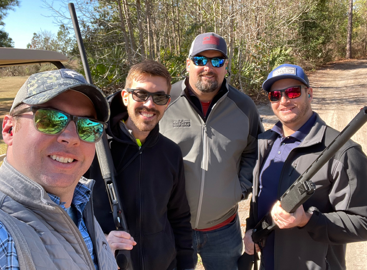 Four team members in jackets smiling and holding guns at our Clay shoot event.