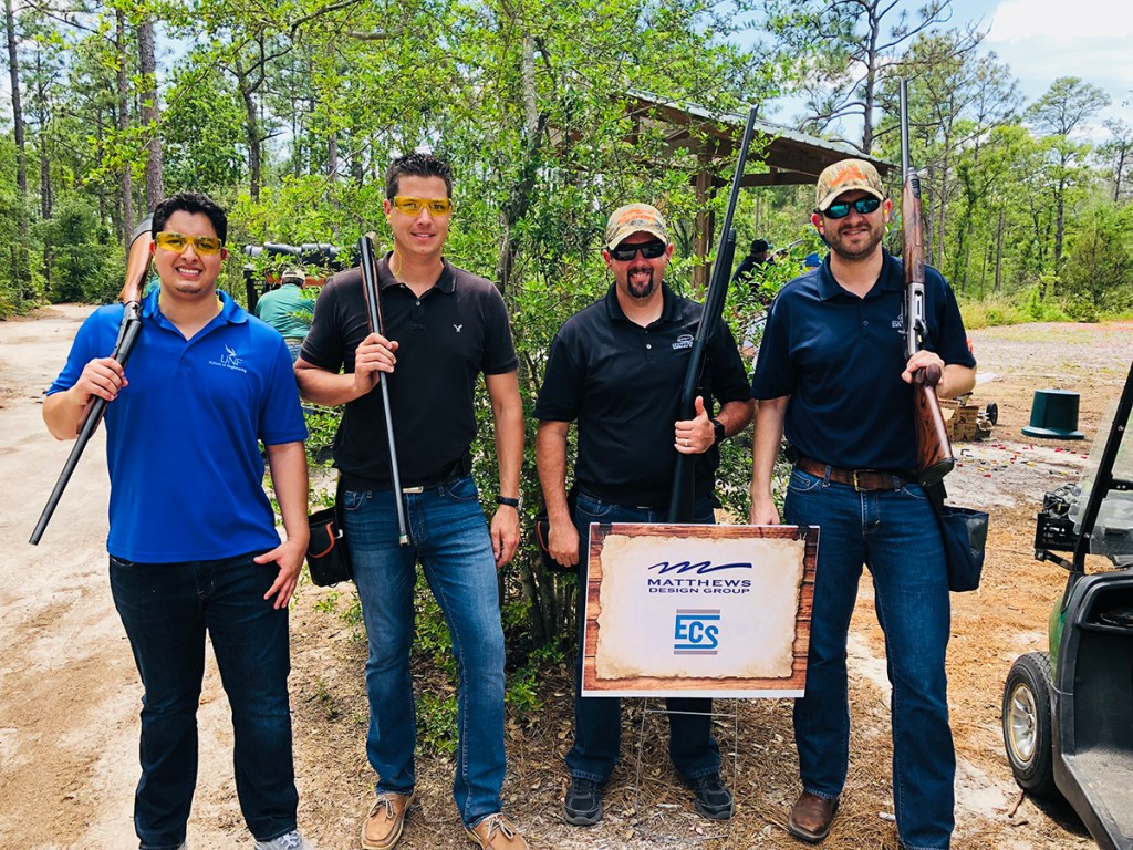 Four team members holding guns smiling during our ECS Shooting event.