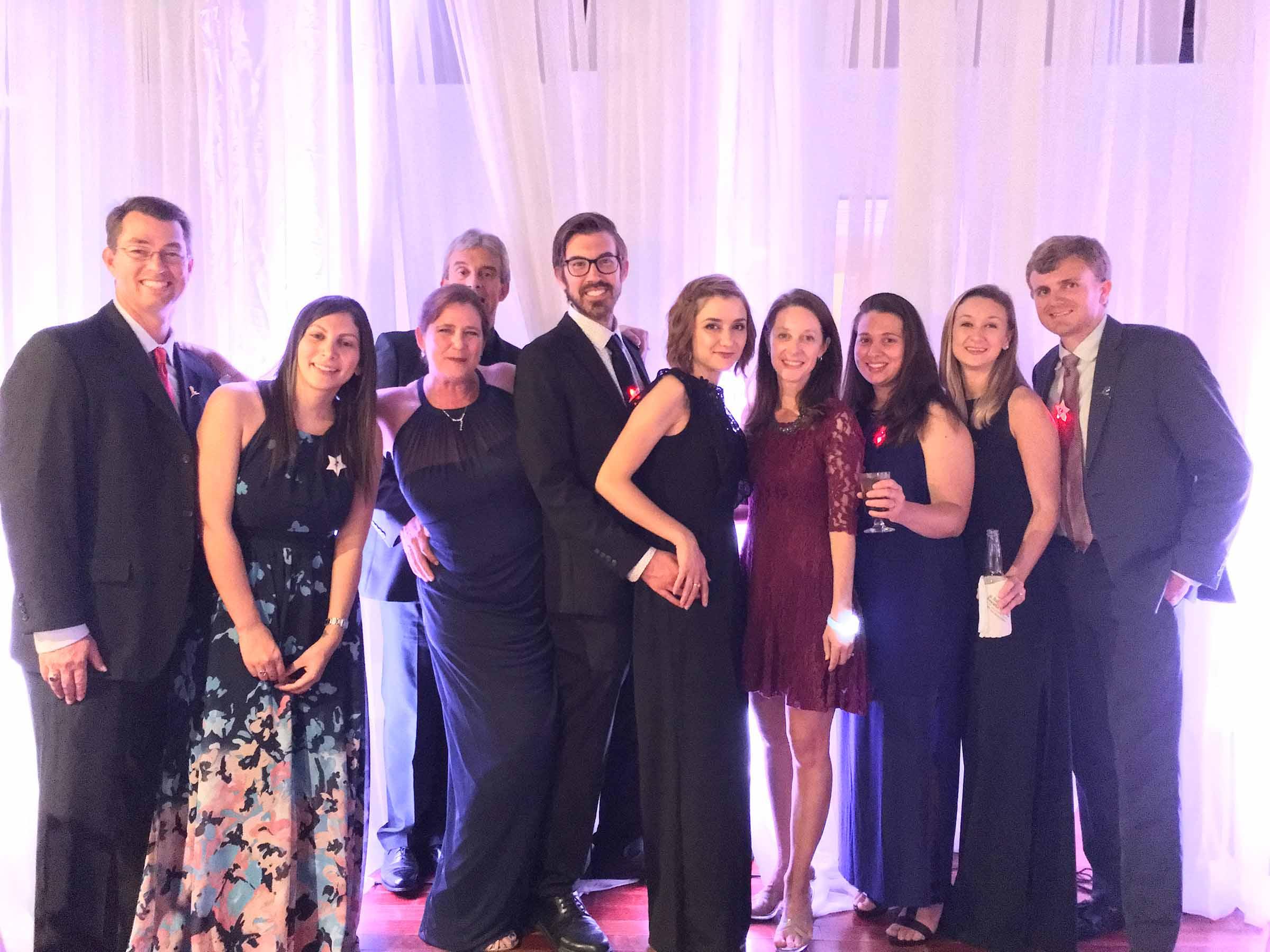 Ten team members smiling in formal dress at the Matthews Design Group formal.