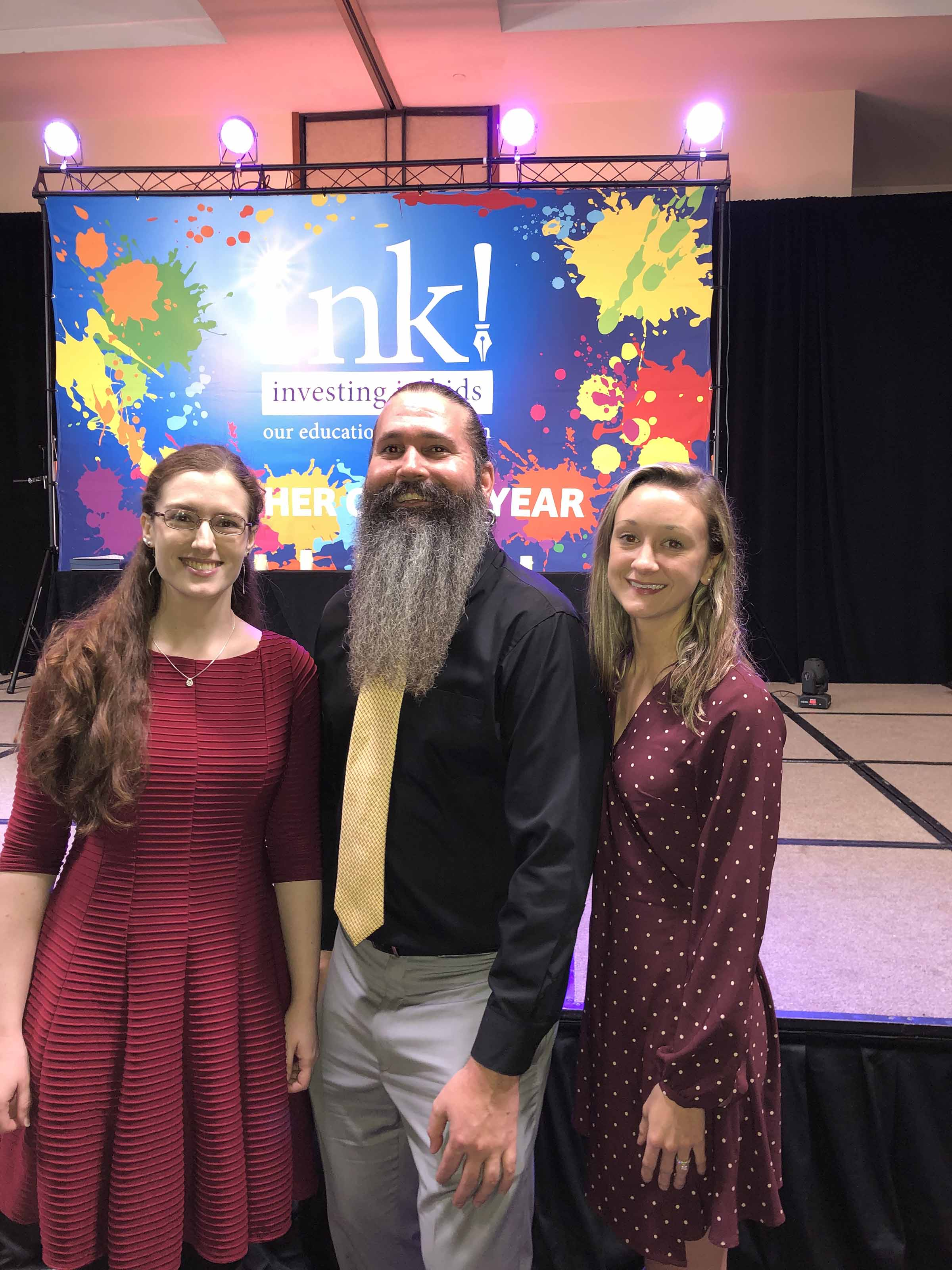 Three team members smiling at Ink Investing in Kids