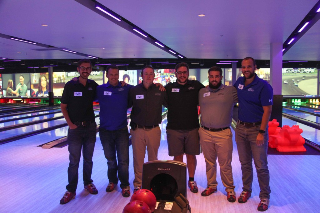 Six team members stand smiling in a bowling alley.