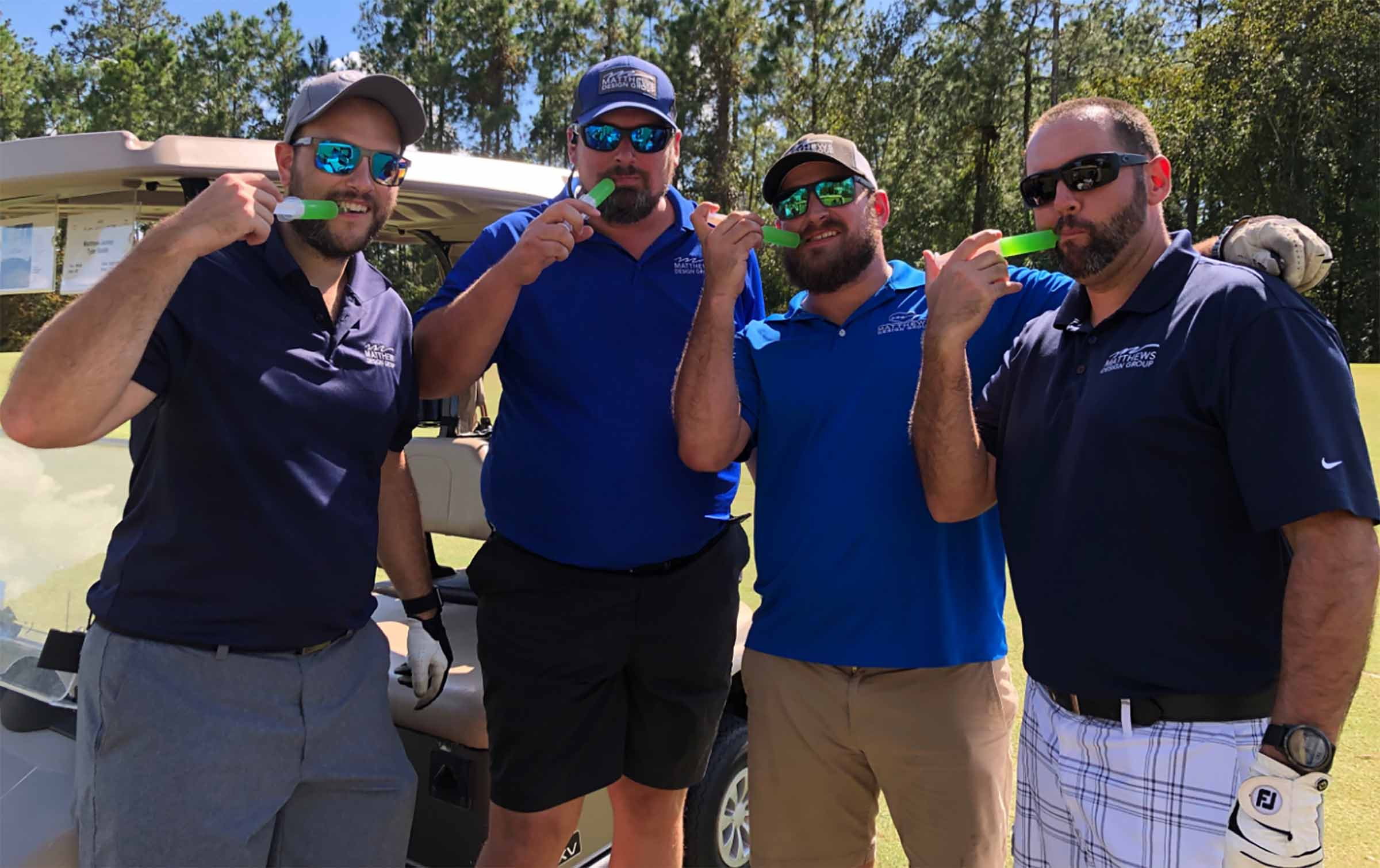 Four Matthews Design Group members standing on a golf course with a jelly syringe in their mouths.