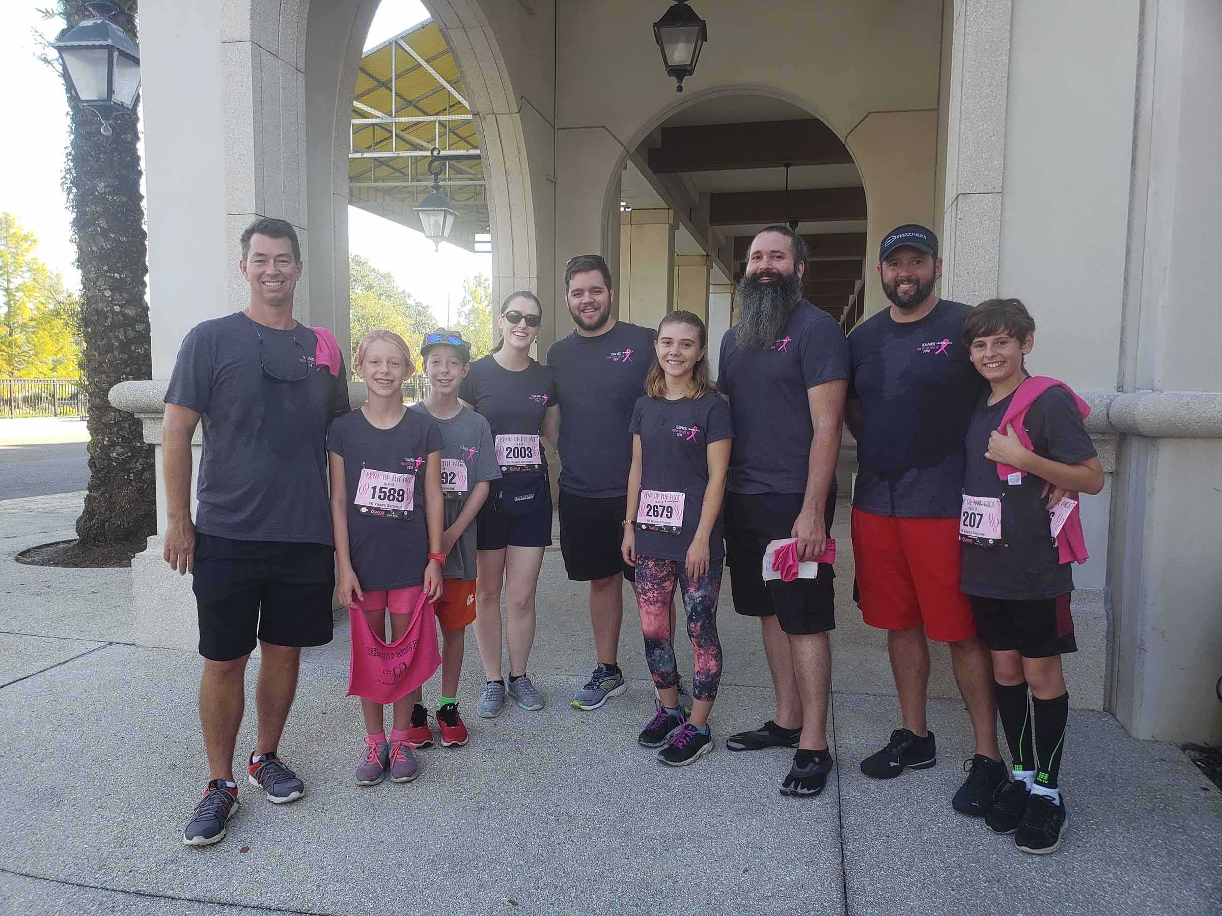 Some team members and their families in running clothes smiling.