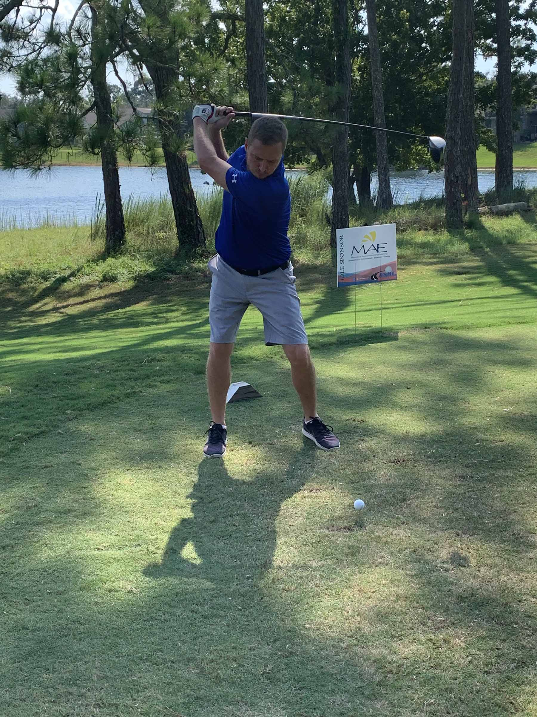 A team member mid-swing on a golf course.
