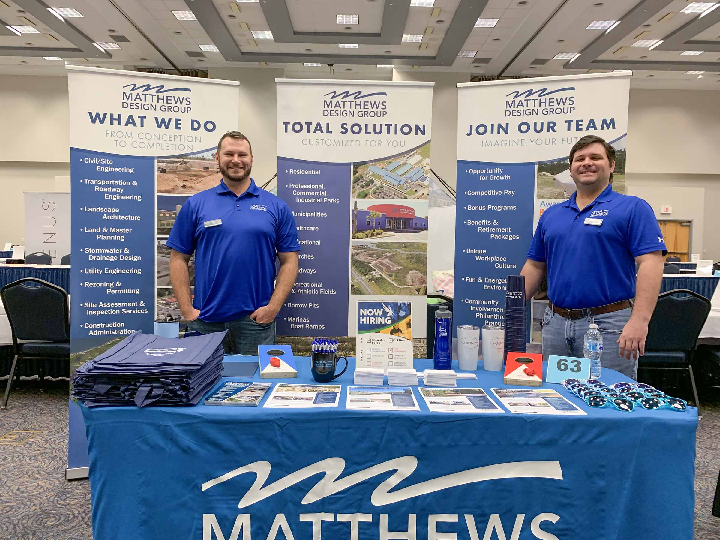 Two team members standing in front of a Matthews Design Group booth smiling.