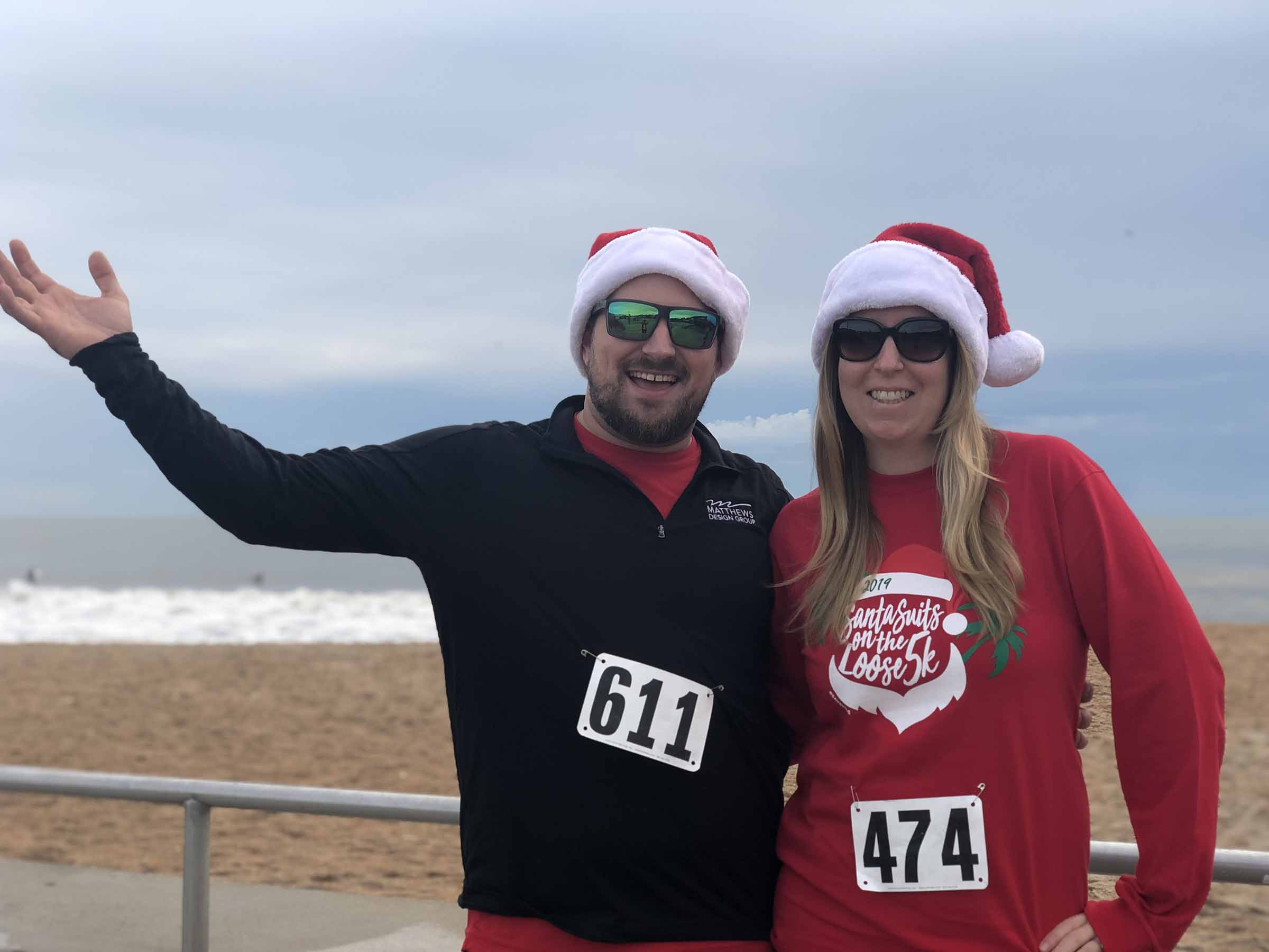 Two team members in front of the beach smiling during the Santa Run 5k.