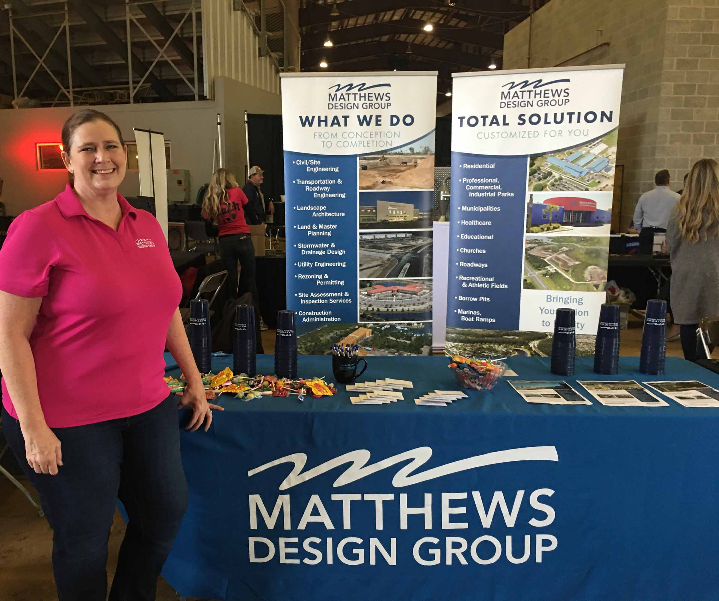 A team member standing in front of a Matthews Design Group Booth.