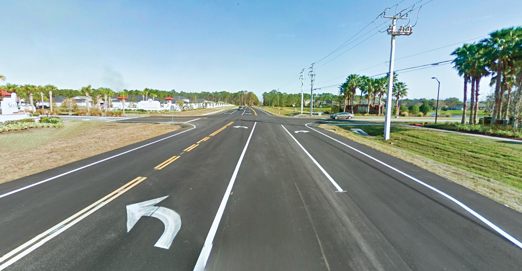 A road with 4 lanes and a subdivision on the left and palm trees surrounding it.