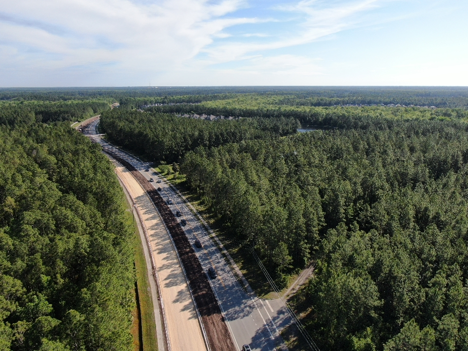 An aerial shot of a two lane road with a road under construction next to it. The road is surrounded by trees and houses in the distance.
