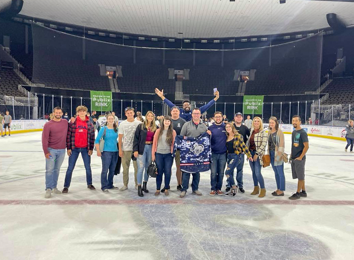 Some Matthews Design Group team members posing and smiling at an ice skating rink.