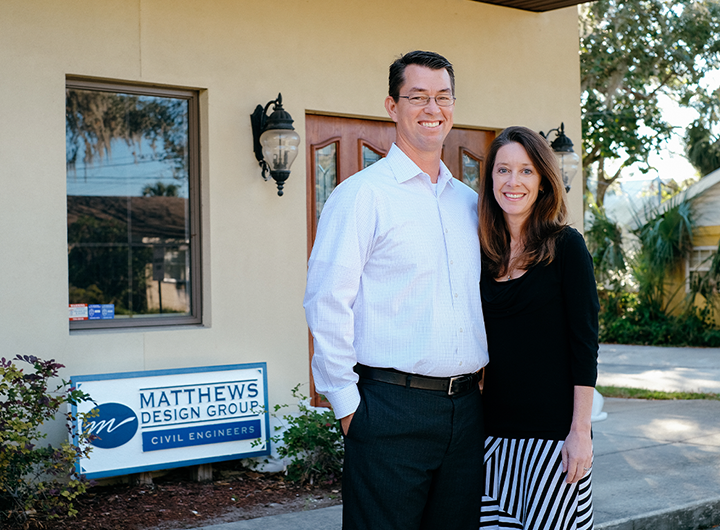Rob and Keri Matthews standing and smiling in front of St. Augustine office location.