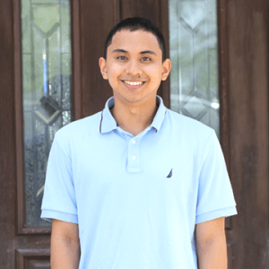 MDG intern Luke Asuncion standing in front of external office doors