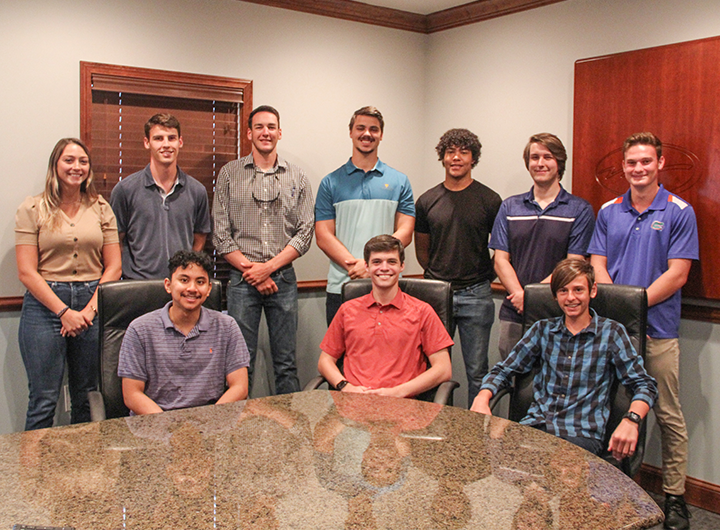 Group of smiling interns gathered behind table in conference room