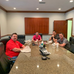 Four people sitting at conference table smiling with breakfast sandwiches in front oof them.