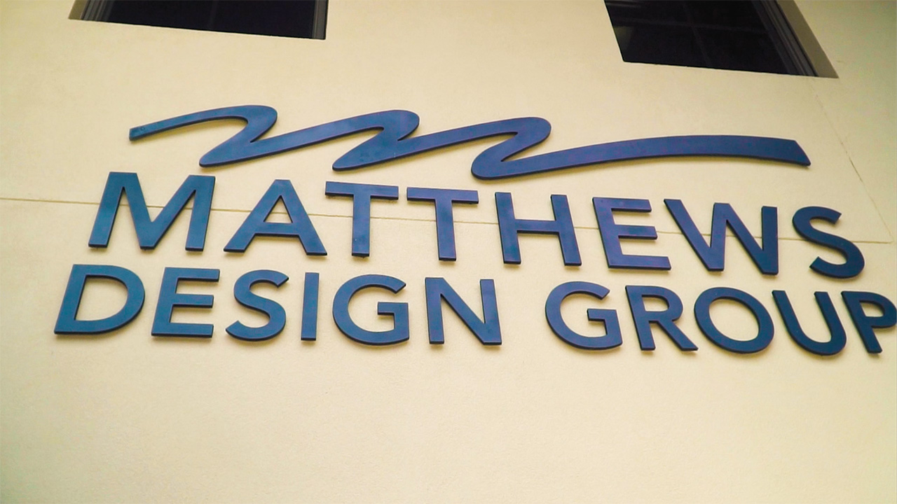 Matthews Design Group sign in blue on the side of the building.